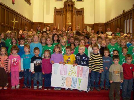 kids hold thank you sign in a church