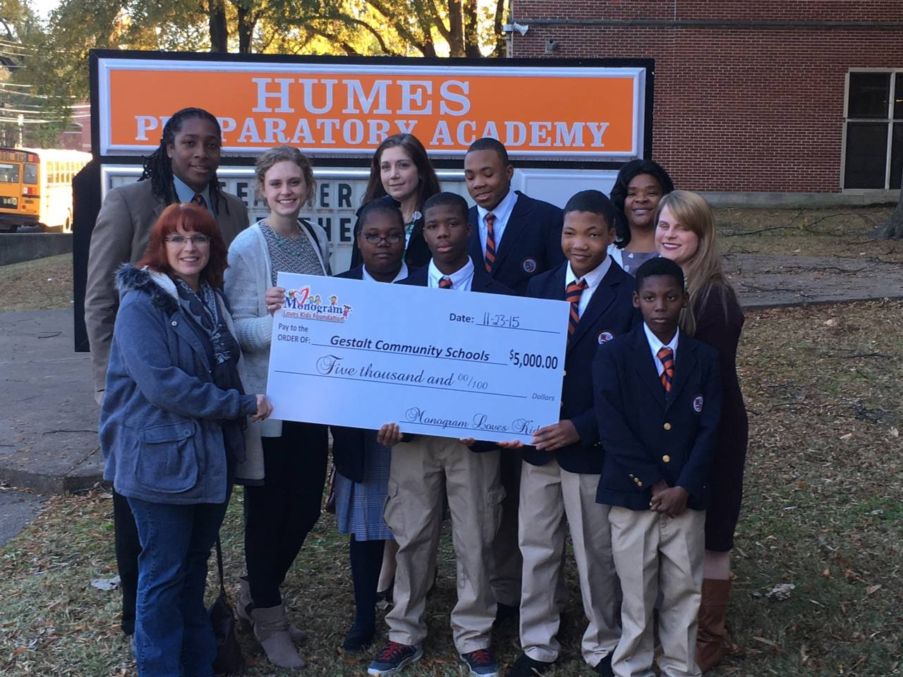 teens from Humes Preparatory Academy hold a novelty check showing a $5,000 donation from the Monogram Loves Kids Foundation