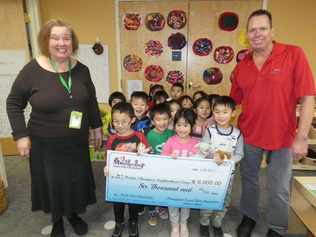 children from Boston Chinatown Neighborhood Center hold a novelty check showing a $6,000 donation from the Monogram Loves Kids Foundation