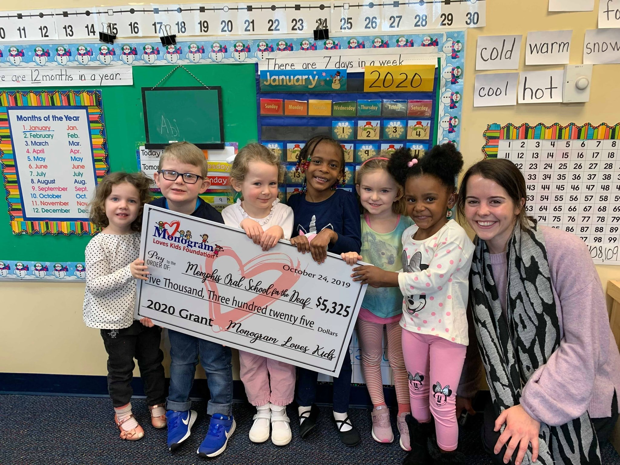 kids from Memphis Oral School for the Deaf hold a novelty check showing a $5,325 donation from the Monogram Loves Kids Foundation