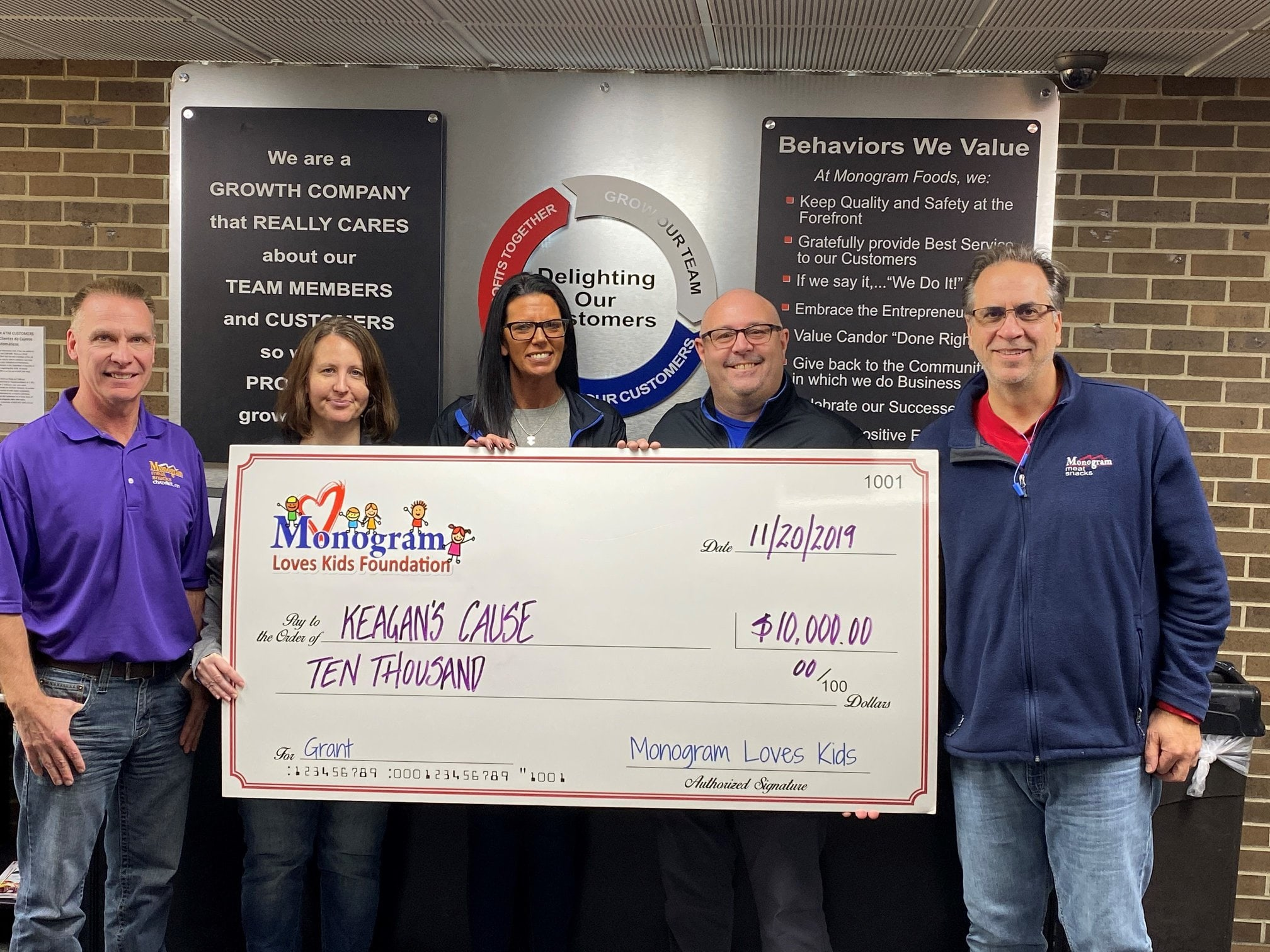 employees from Keegan's Cause hold a novelty for a $10,000 donation from the Monogram Loves Kids Foundation