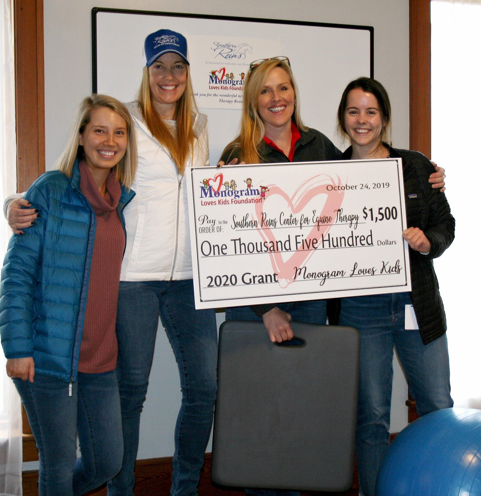 employees from Southern Reins Center for Equine Therapy hold a novelty check for a $1,500 donation from the Monogram Loves Kids Foundation