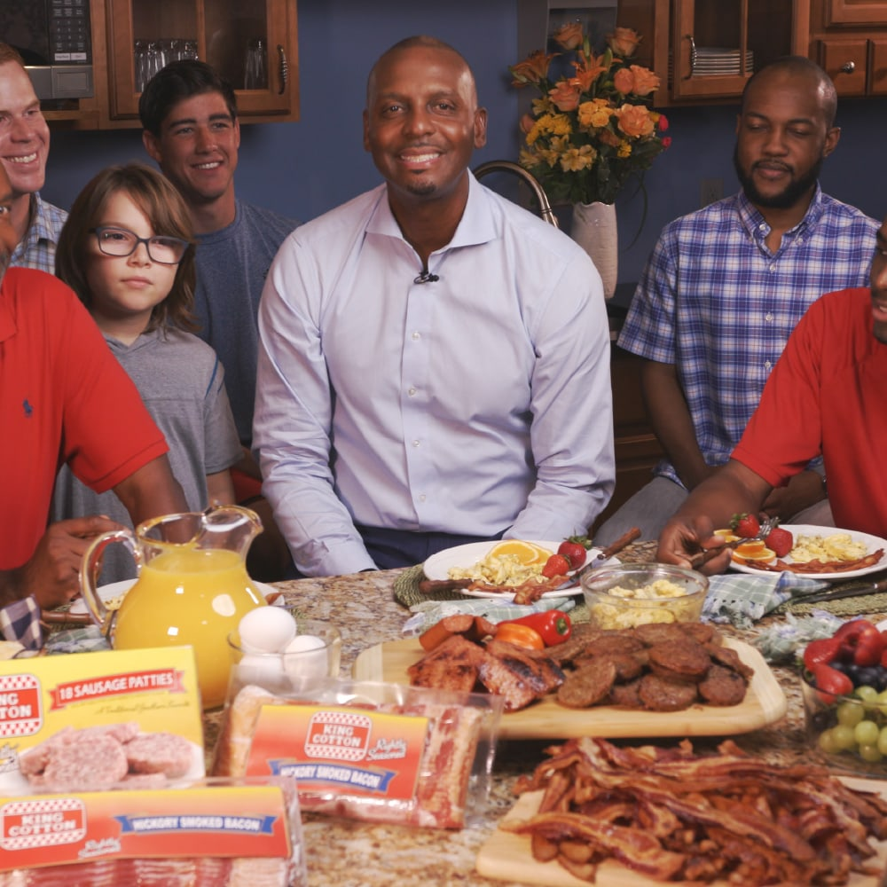 Penny Hardaway and friends sit around a table full of King Cotton foods from Monogram