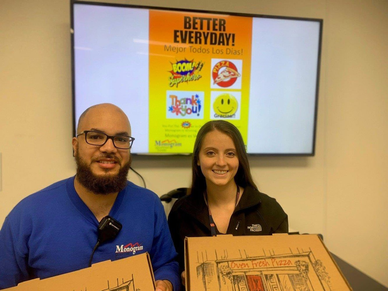 Monogram employees hold pizza boxes during pizza party